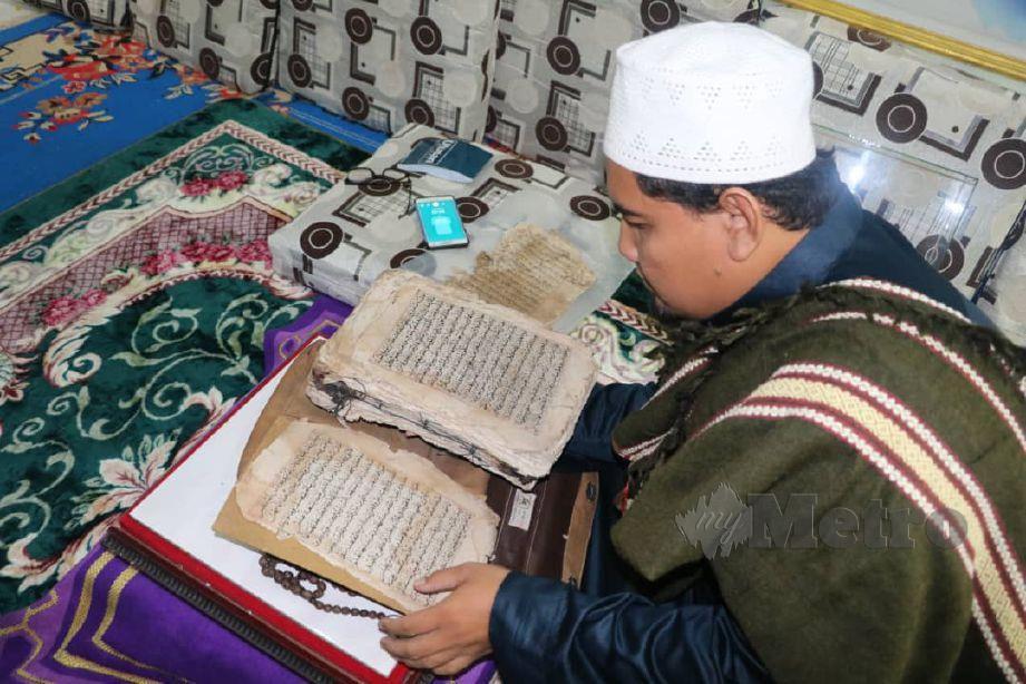 BARKATULLAH Mohd Bahari, 37, meneliti  Al- Quran bertulisan tangan berusia hampir 300 tahun ketika ditemui di pondok Raudhah Al-Muhibin Kampung Pantai Seberang Chenor. FOTO Roselan Ab Malek