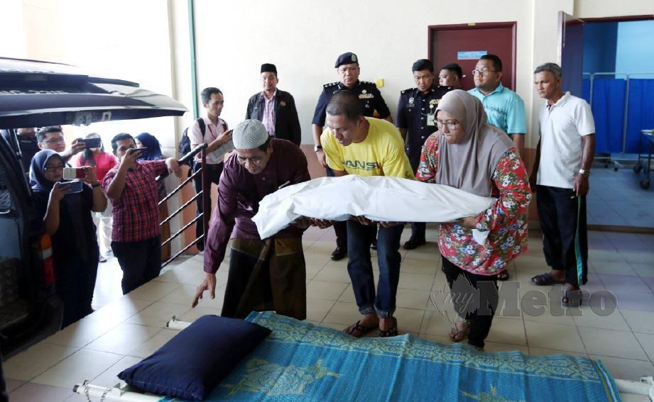 LANS KOPERAL Ahmad Hafiz Mustafa, 32, (tengah) bersama isterinya, Sofiah Mohd Teridi, 32, memangku jenazah anaknya, Muhamad Anas Hadif, 3, keluar selepas dikapankan di Jabatan Forensik Hospital Raja Permaisuri Bainun Ipoh. FOTO Muhaizan Yahya