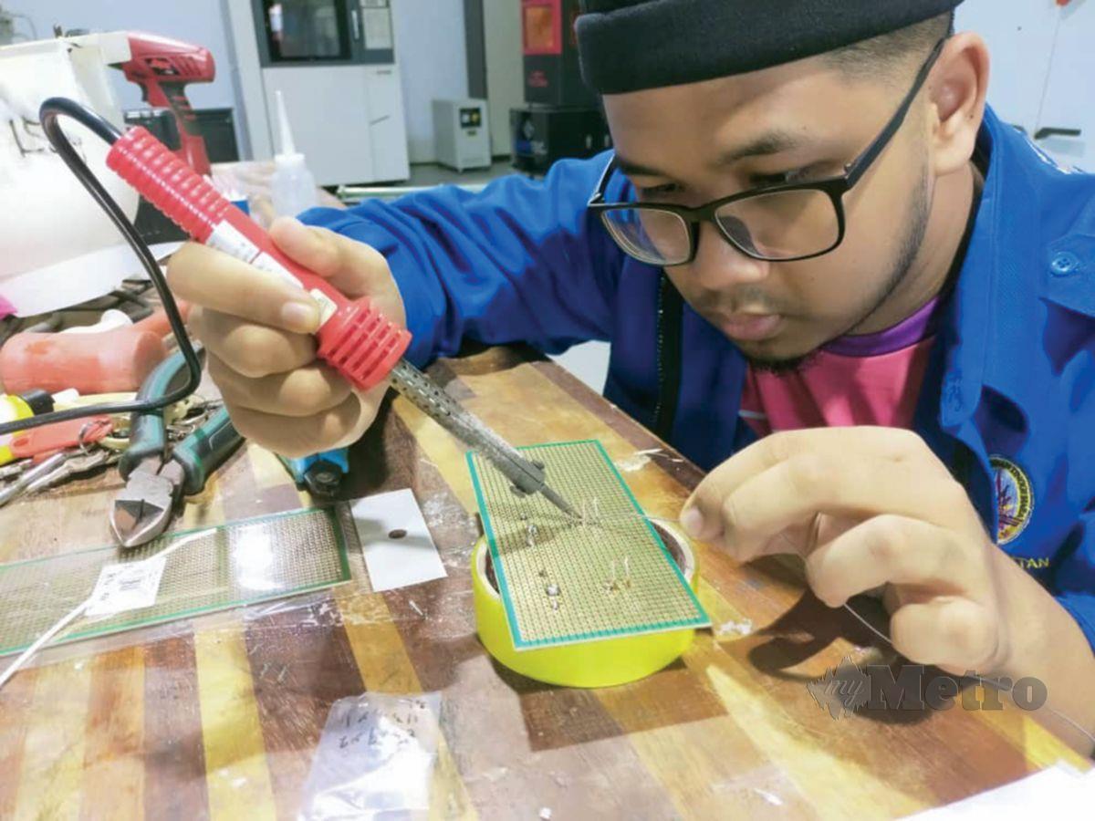 HOOD Haqqi menyiapkan salah satu komponen dalam tugasannya.