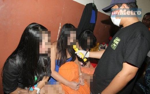 ANGGOTA penguat kuasa AADK memeriksa seorang wanita yang ditahan.