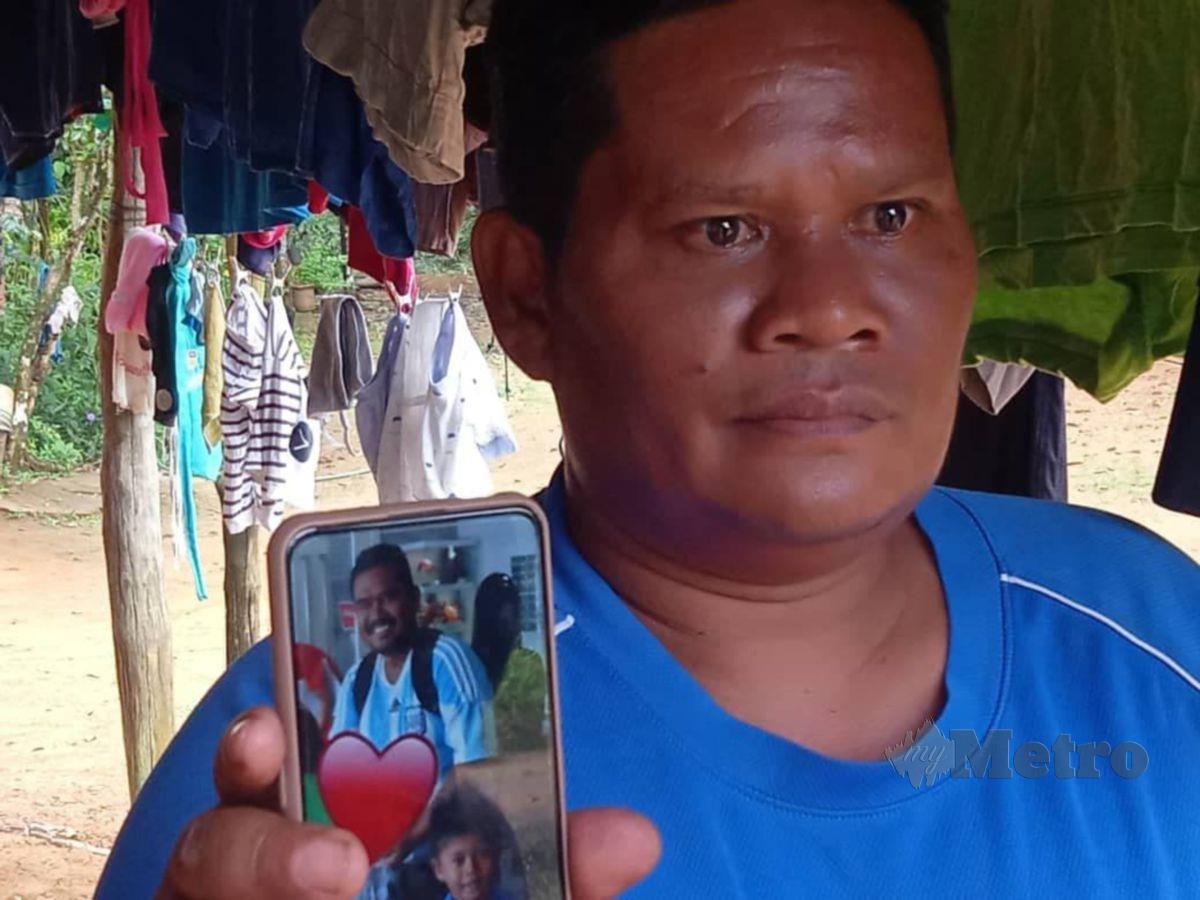 ZARIMAN menunjukkan gambar adiknya yang  cedera parah terkena tembakan  ketika sedang bertugas di pos keselamatan Malaysia-Thailand dekat Padang Besar. FOTO ROSELAN AB MALEK