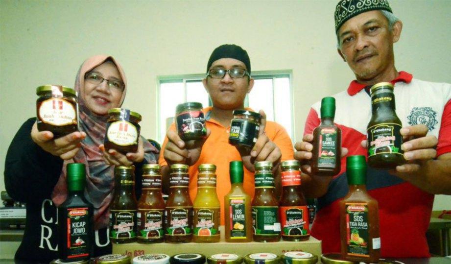 MUHAMMAD Hafid (tengah) bersama ibunya, Amaruszati dan bapa, Mohd Azli menunjukkan produk keluaran syarikatnya.