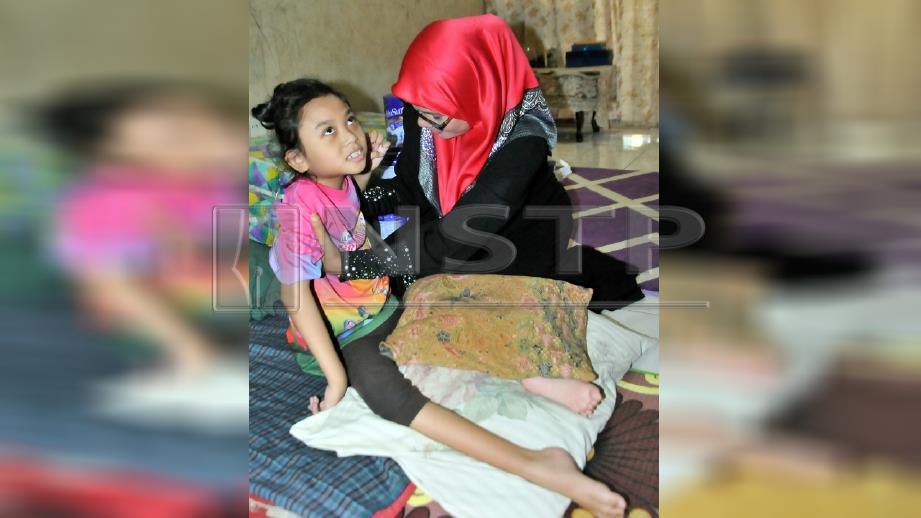 Nour Rabiatul Adawwiyah Iman dipangku Rohaidatul Asma yang hadir beri sumbangan. FOTO Shaiful Shahrin Ahmad Pauzi.