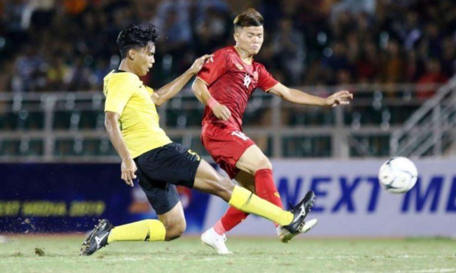 AKSI pemain negara (kiri) cuba mengekang kelincahan pemain Vietnam di Stadium Thong Nhat, Ho Chi Minh. - FOTO AFF