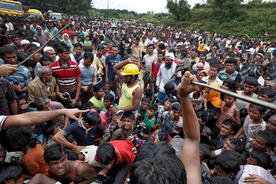 Petugas yang mengedarkan bantuan terpaksa menggunakan kekerasan bagi mengawal pelarian Rohingya yang bersesak mengambil barangan bantuan. - Foto REUTERS