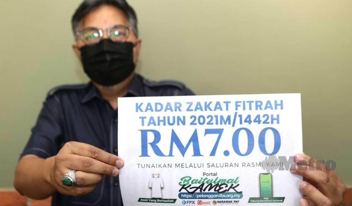 ABANG Mohammad Shibli menunjukan kadar zakat fitrah, yang telah ditetapkan oleh Jabatan Mufti Negeri Sarawak bagi Ramadhan 2021 sebanyak RM 7.00 untuk seorang di Dewan Utama Saidina Umar Al-Khattab, Ibu Pejabat Tabung Baitulmal Sarawak, Batu Kawa. FOTO Nadim Bokhari