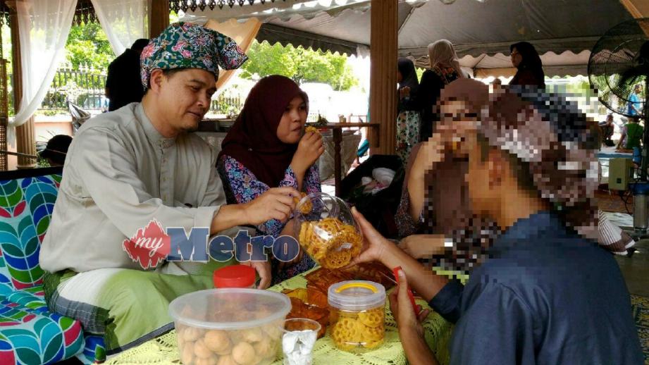 AKMAL (kanan) menghulurkan kuih raya kepada Hafiz pada Majlis Rumah Aidilfitri AADK Kuala Terengganu. FOTO Nazdy Harun