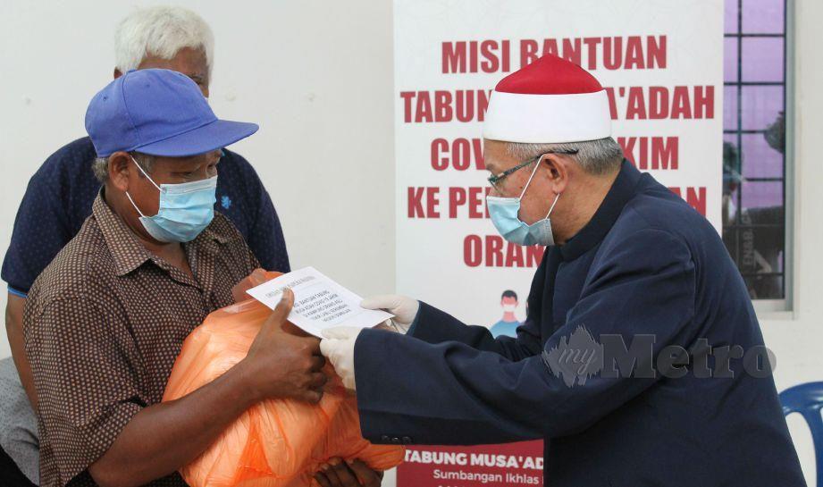 ZULKIFLI (kanan) menyerahkan bantuan makanan dan wang tunai kepada penduduk Kampung Orang Asli Tekir. FOTO Mohd Amin Jalil