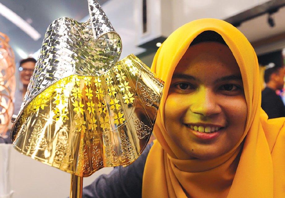 WAN Nur Azren Syarina bersama lampu meja bermotifkan songket yang dihasilkannya.