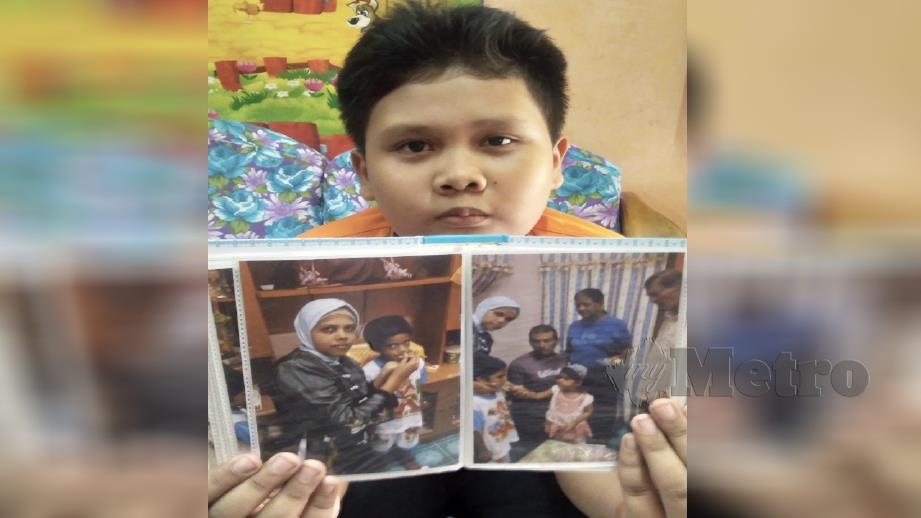 Mohd Aiman Syukur menunjuk gambar ibunya yang dilaporkan hilang di Tamil Nadu, India sejak 29 Jun lalu. Foto Rosman Shamsudin