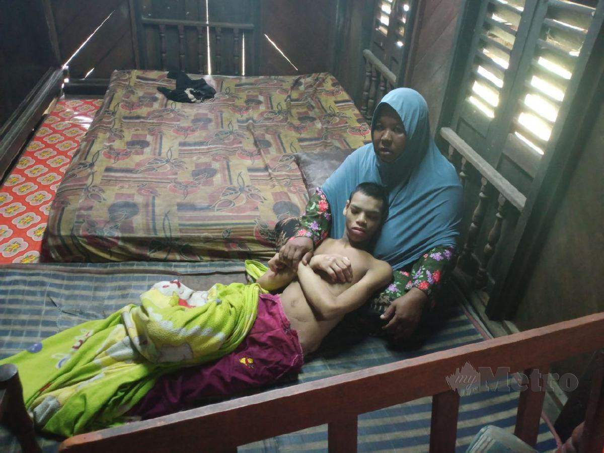 SITI KHOLIJAH bersama anak istimewanya, Muhammad Fawwaz di rumah yang ditumpangi mereka di Kampung Padang Lalang, Bahau. FOTO MOHD KHIDIR ZAKARIA