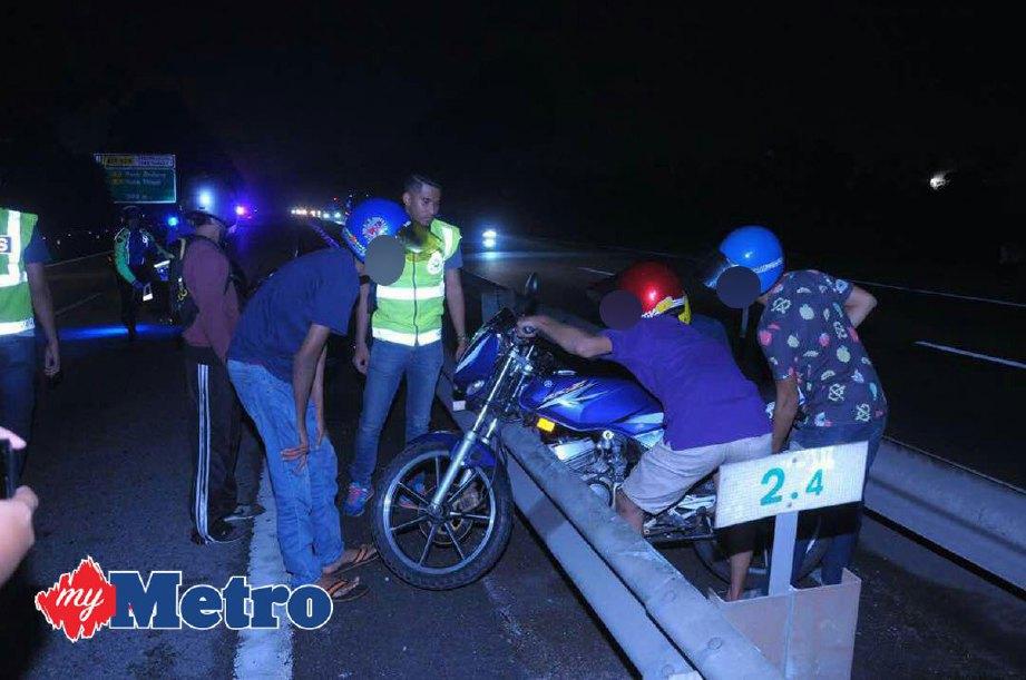 Mat rempit ditahan polis ketika cuba mengangkat motosikal melepasi besi penghadang di Lebuhray PLUS berdekatan Taman Setia Tropika, Johor Bahru ketika digempur polis trafik awal pagi ini. FOTO Mohamad Azhari Jaafar