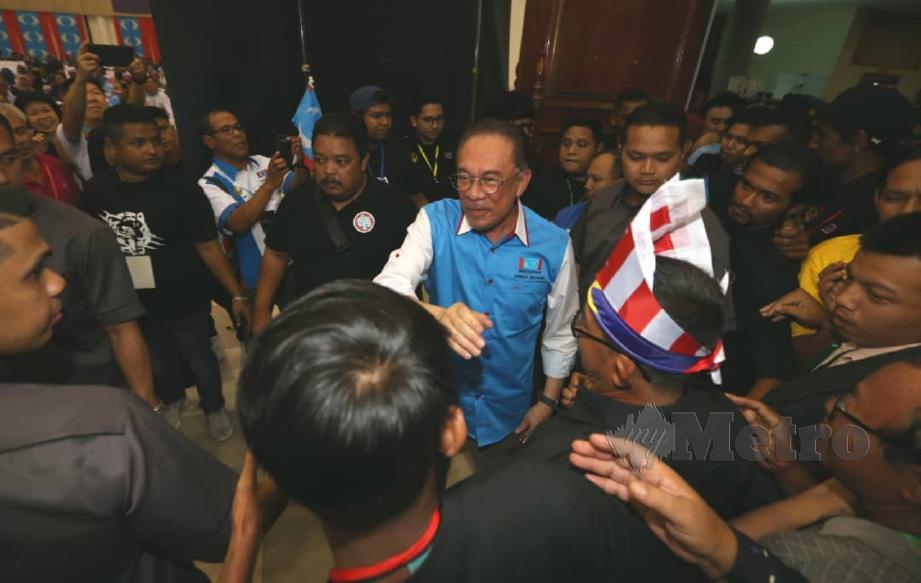 ANWAR (tengah) bersalaman dengan orang ramai ketika hadir merasmikan Konvensyen PKR Perak di Dewan Jubli Perak di Kuala Kangsar, malam tadi. FOTO Muhaizan Yahya