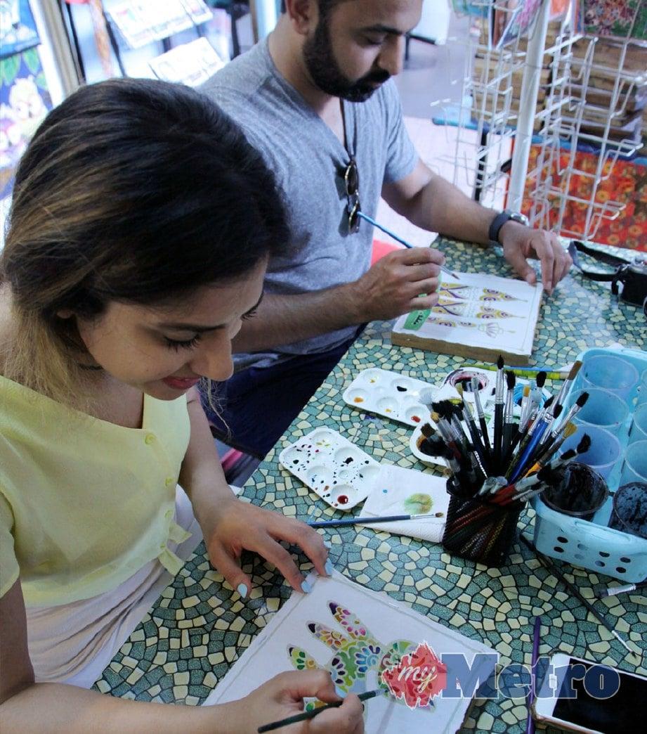 PELANCONG diberi peluang melukis pada silk screen batik dengan dikenakan bayaran RM15. FOTO Nik Hariff Hassan