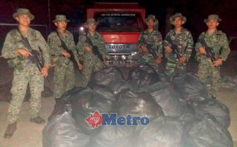 ANGGOTA Pasukan 4 Rejimen Sempadan (4RS) menunjukkan bungkusan daun ketum dirampas dianggarkan bernilai RM55,000 di Pos Sahara, Padang Terap, awal pagi semalam. FOTO ihsan ATM.