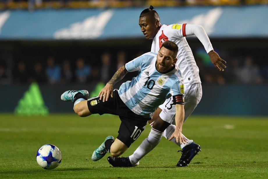MESSI (kiri) dijatuhkan pemain Peru, Pedro Aquino. FOTO/AFP