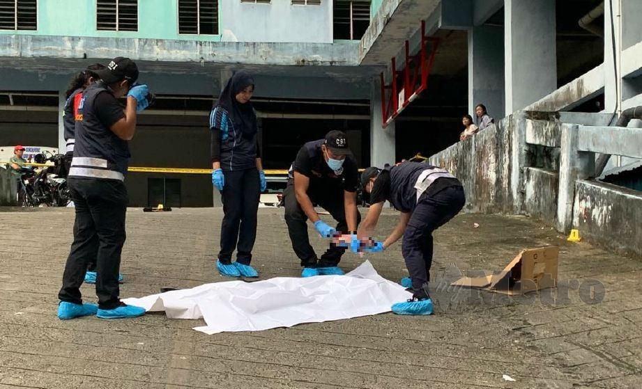 ANGGOTA polis mengangkat mayat bayi yang dicampak dari tingkat 13 sebuah apartmen. FOTO Audrey Dermawan
