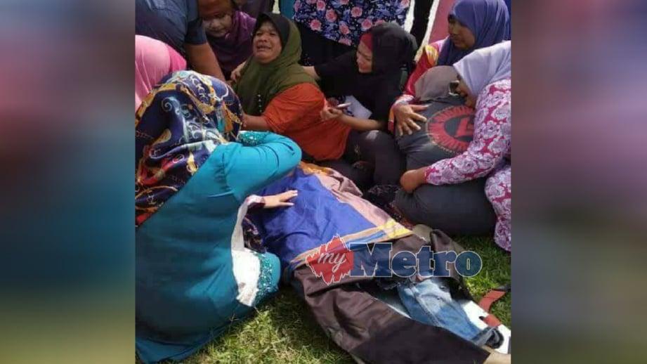 AHLI keluarga melihat mangsa yang maut akibat kemalangan di Kampung Sungai Dua, Bachok, hari ini. FOTO Ihsan Pembaca