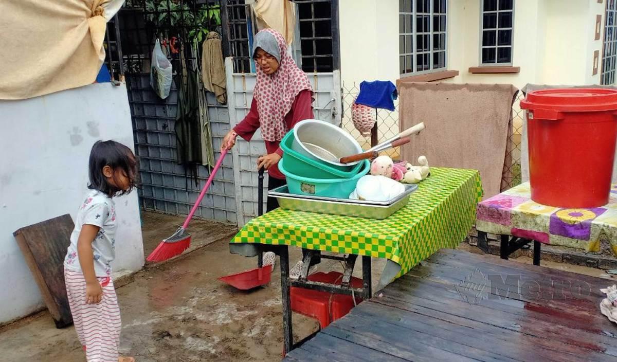 NURUL Fadhilah membersihkan bahagian dapur dan peralatan di rumahnya yang dilanda banjir. FOTO Malik Muhamad
