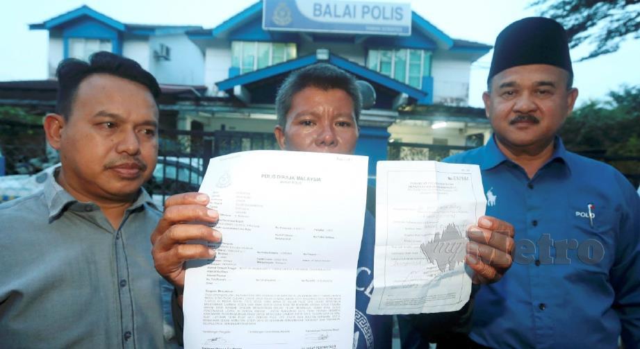 A Bakar (tengah) menunjukkan laporan polis selepas tular tidak benar mendakwa kematian Marini akibat pencemaran Sungai Kim Kim, sedangkan doktor mengesahkan kematiannya akibat masalah jantung. FOTO HAIRUL ANUAR RAHIM