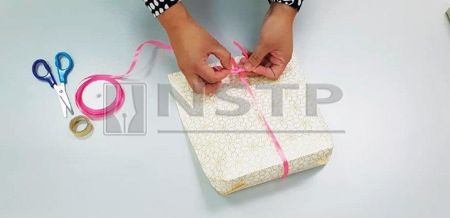8. ISIKAN barangan di dalamnya, lipat hujung pembalut dan cantum dengan pengokot. Hiaskan dengan reben sama ada membalut keseluruhan bungkusan atau dilekat di hujung bungkusan.