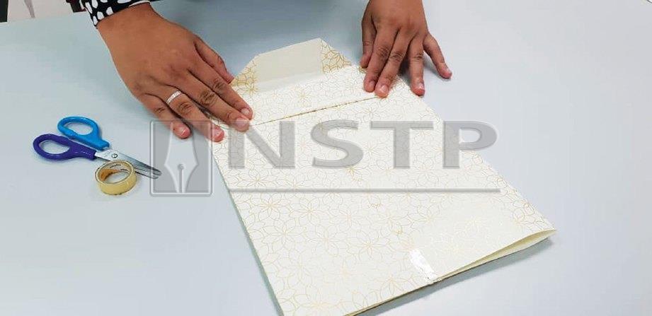 6. AMBIL hujung lipatan kedua-dua bahagian dengan salah satunya menindih bahagian satu lagi.