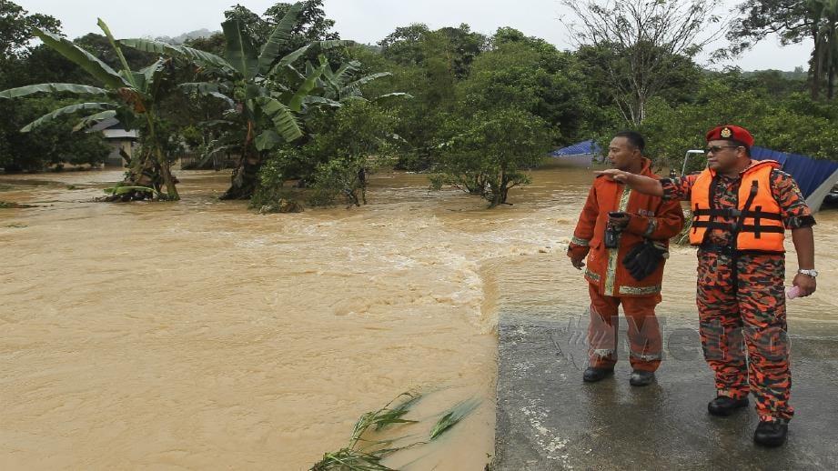 Hamdan (kanan) meninjau kawasan yang mengalami banjir kilat di Kampung Bemban, Mambau dekat Seremban. Foto Azrul Edham Mohd Aminuddin