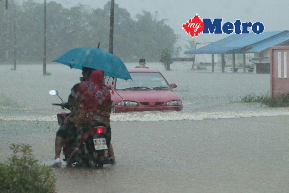 Kenderaan melalui jalan menuju ke Kampung Bendang Pak Yong yang mula dinaiki air berikutan hujan lebat sejak beberapa hari lalu. FOTO SYAMSI SUHAIMI