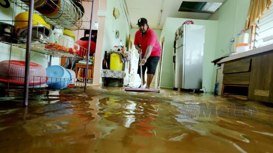 Yuszerin Mat Yunus, 37, membersihkan lantai rumahnya selepas banjir surut di Kampung Bukit Datuk A, Tanjung Minyak. FOTO Khairunisah Lokman