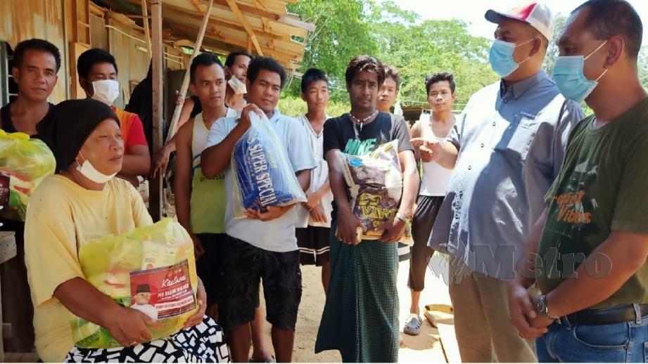 MOHAMAD Sahabudin (dua kanan) menyampaikan bantuan barangan makanan kepada warga asing. FOTO Safuri Kamarudin.