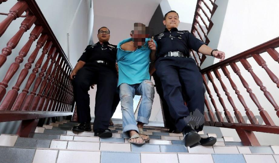 TERTUDUH dibawa keluar selepas dijatuhi hukuman penjara 20 tahun dan 24 sebatan. FOTO Rasul Azli Samad.