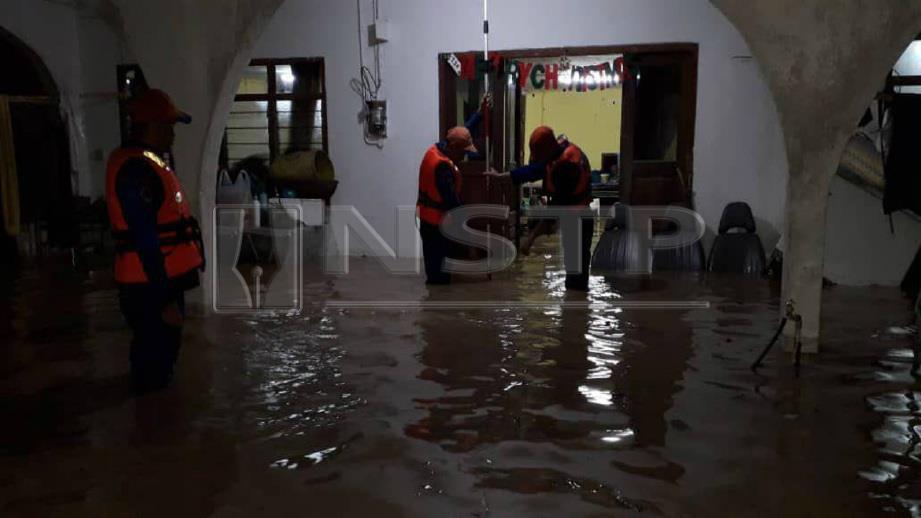 ANGGGOTA Angkatan Pertahanan Awam Malaysia (APM) Bau memantau keadaan banjir yang melanda Kampung Jugan, Bau akibat hujan lebat, semalam. Foto Ihsan JBPM