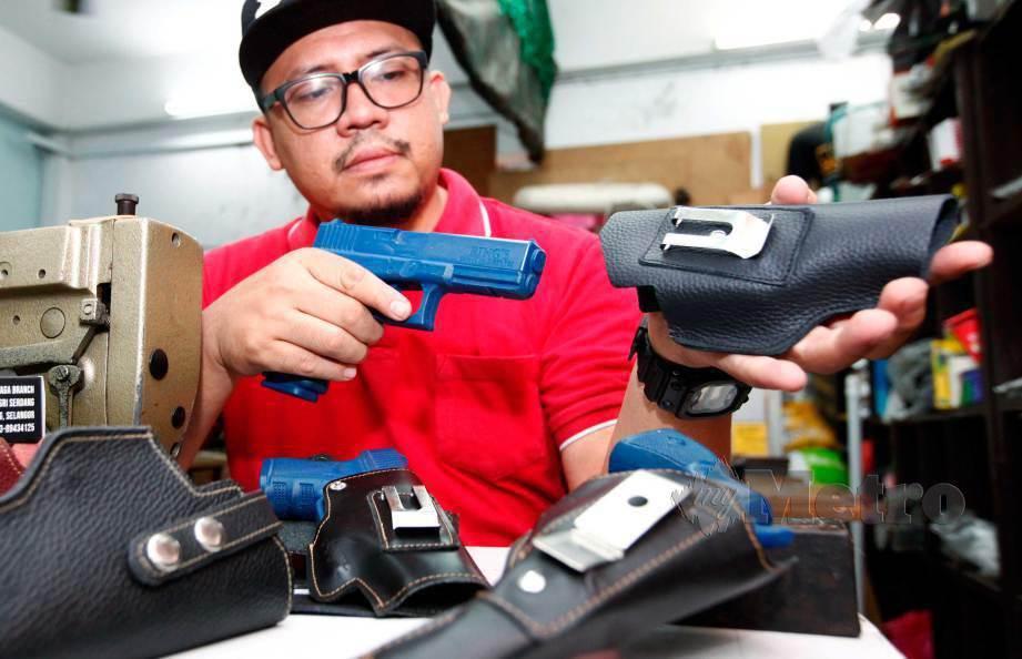 MUHAMAD Faisal menunjukkan sarung pistol yang sudah siap. FOTO Hasriyasyah Sabudin