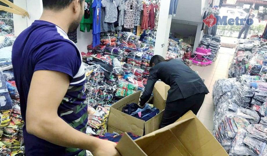 PEGAWAI KPDNKK melakukan pemeriksaan di premis yang menjual pakaian cetak rompak diserbu di Jalan Kenanga, semalam. FOTO NSTP