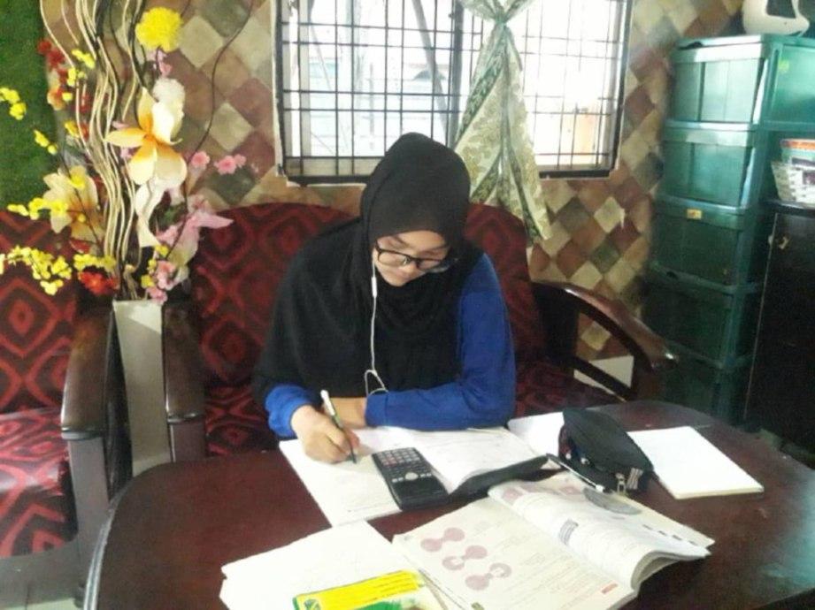 FATIN Najwa Abdullah, 16, membuat kerja sekolah diberikan gurunya melalui aplikasi dalam talian.