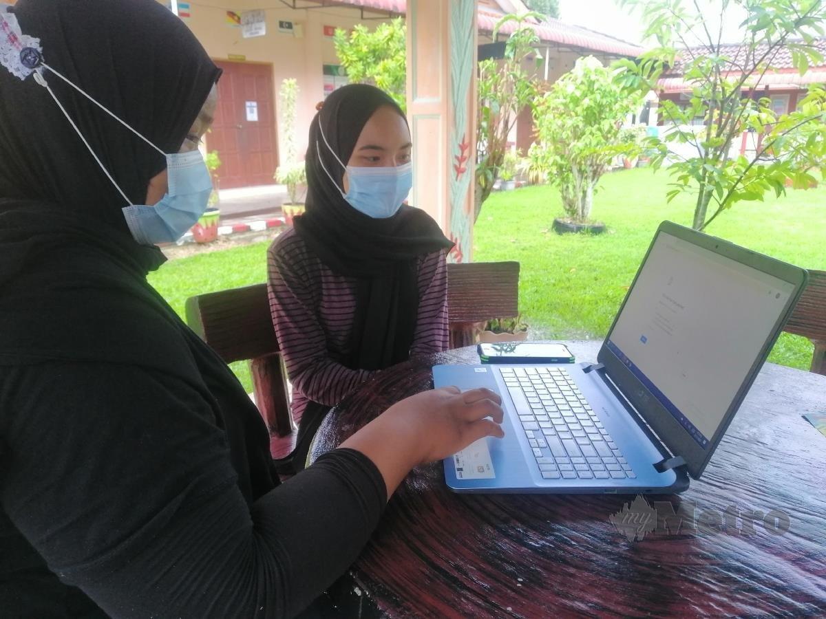 NUR AIN bersama Nur Syazana kecewa dengan rangkaian internet di PPS SK Parit Haji Aman yang lemah dan menyukarkan mereka membuat kerja sekolah dan mengikuti kelas secara dalam talian. FOTO SHAIFUL SHAHRIN AHMAD PAUZI
