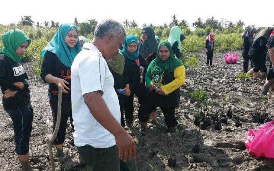 PESERTA mendapat bantuan daripada kakitangan Jabatan Perhutanan Kedah mengenai cara menanam.