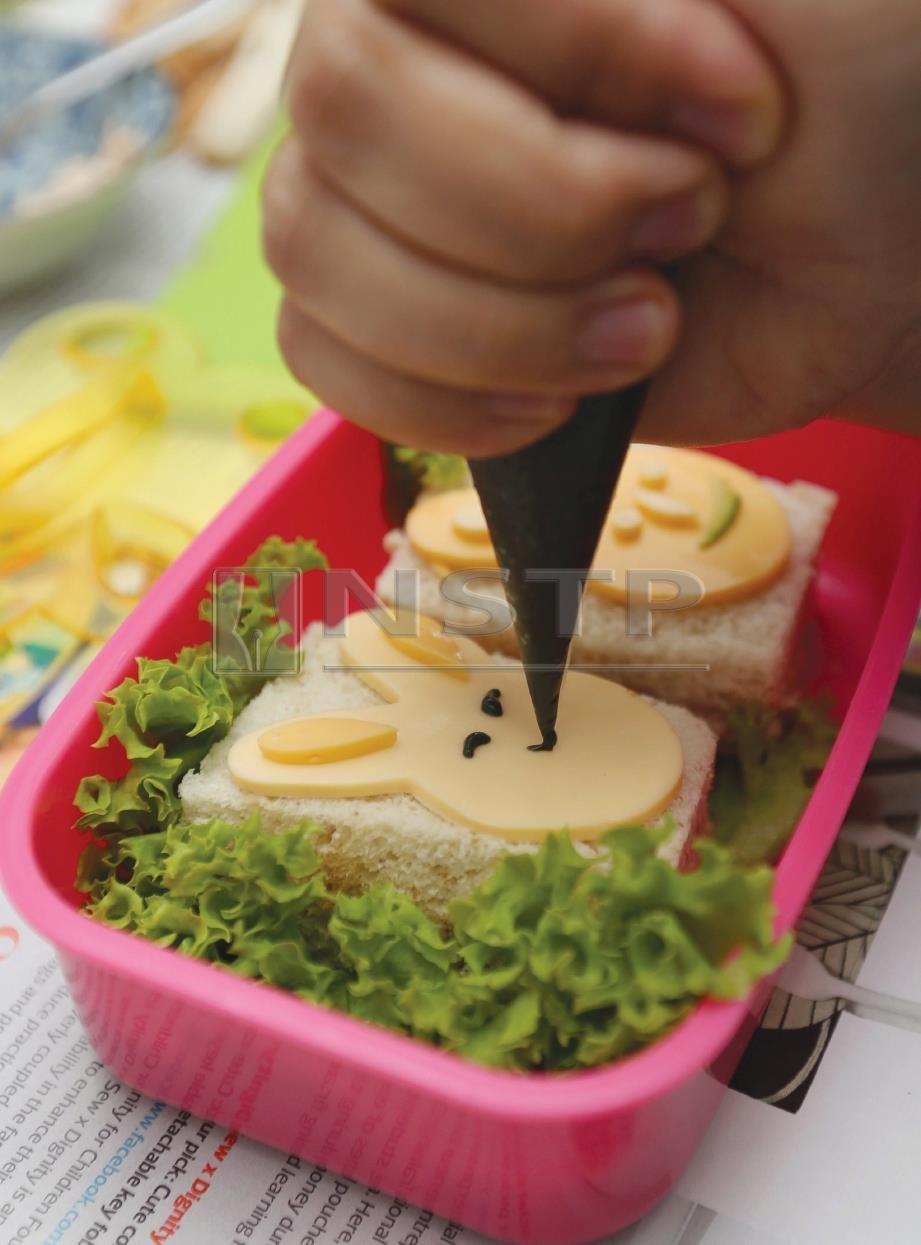 6. AMBIL pewarna makanan hitam campurkan bersama mayonis kemudian lukis mengikut bentuk mata, hidung dan mulut. FOTO Zunnur Al Shafiq.