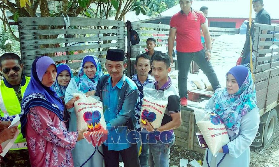 Azmi (tiga dari kanan) menyerahkan sekampit beras kepada tetamu yang hadir ke majlis perkahwinan anaknya. FOTO Azlan Hafeedz