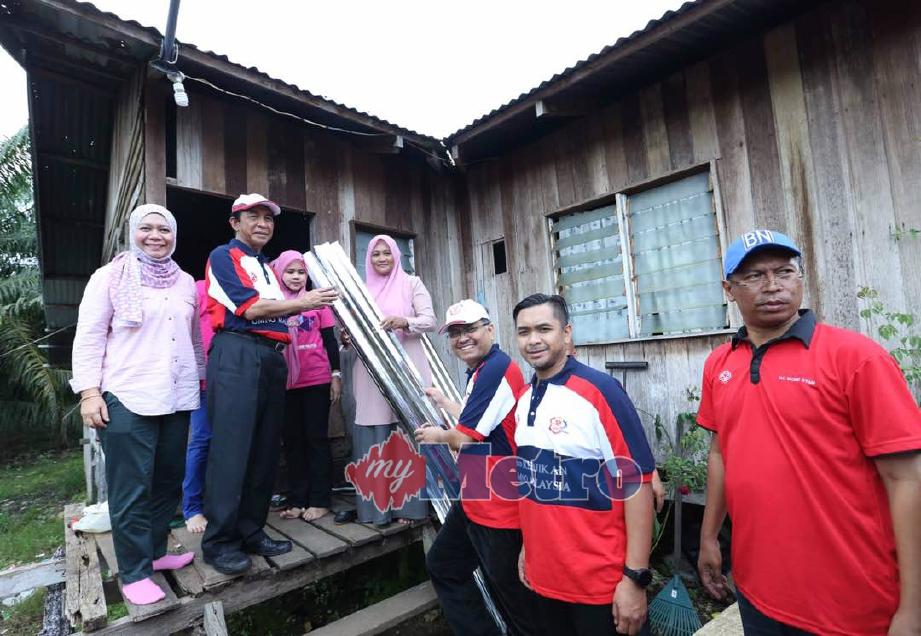 Shamsul Anuar (tiga kanan) menyerahkan sumbangan kepada Mariani dalam kunjungan sempena program UMNO Bantu Rakyat 2.0, hari ini. FOTO Rosela Ismail