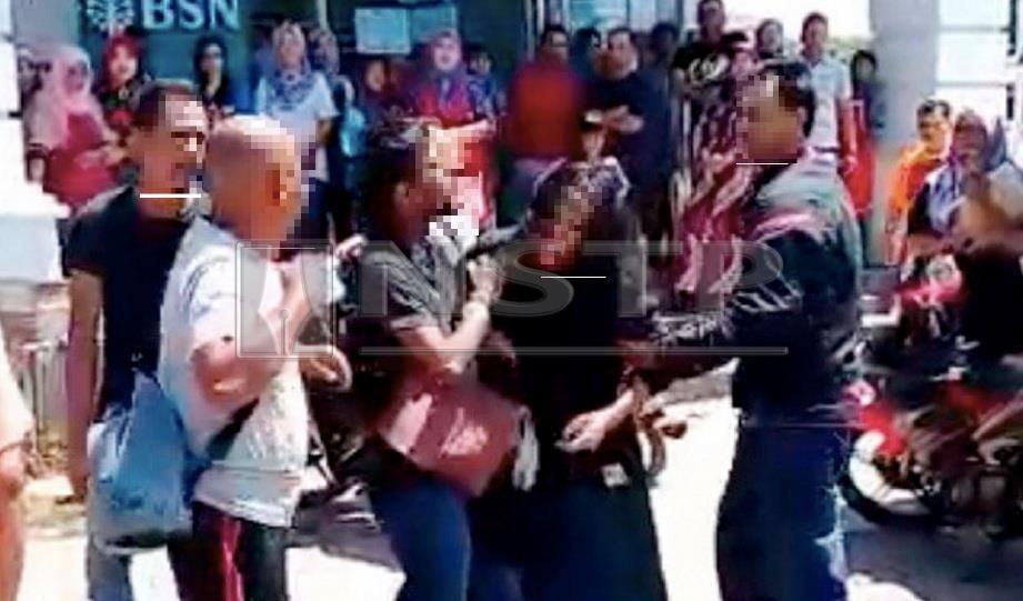 LELAKI dipercayai menjalinkan hubungan dengan isteri orang (tengah) cuba menarik wanita terbabit sambil beberapa orang mahu memukulnya di pekan Kuala Besut, Jertih, hari ini. FOTO ihsan pembaca
