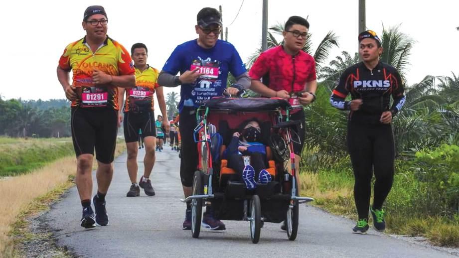 WIRA SUDEPJA berlari sambil menolak Nur Wadihan dalam basikal roda tiga.