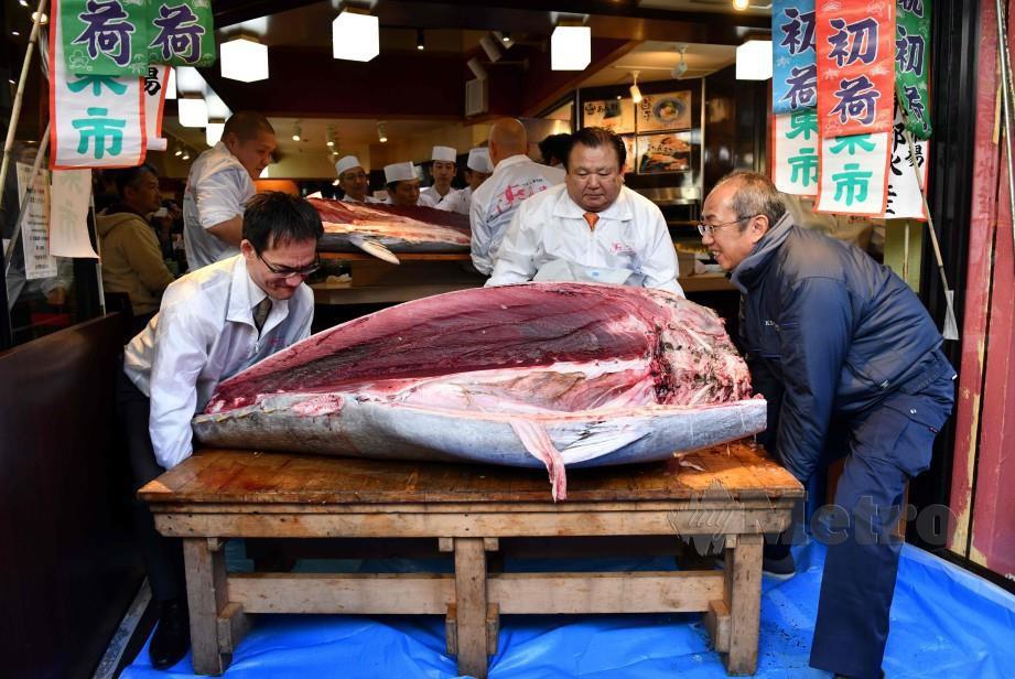 KIMURA (tengah) bersama ikan tuna gergasi yang dibelinya dengan harga RM7.3 juta. FOTO AFP