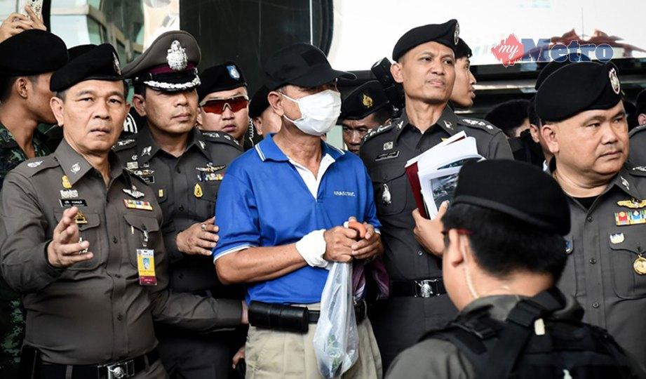 GAMBAR fail, Wattana Phumret diiring anggota polis ketika di mahkamah. FOTO AFP