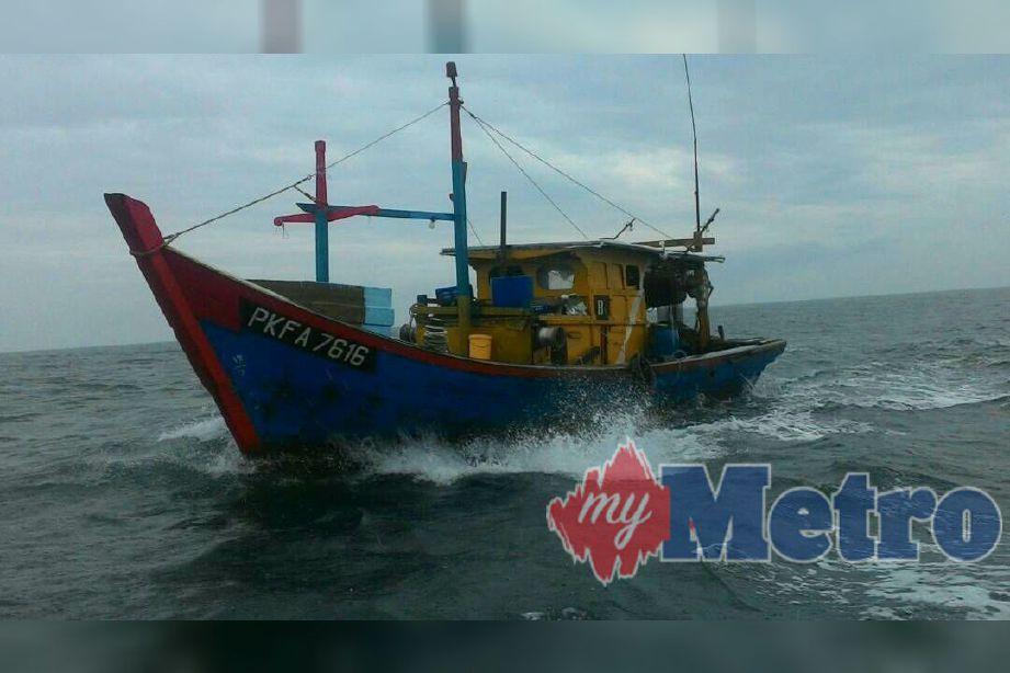Bot nelayan tempatan bersama dua nelayan warga Myanmar yang ditahan APMM. Foto ihsan APMM.