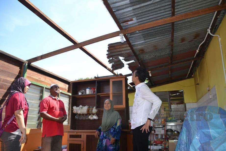 NORLAILA Awang (kiri) dan Mohd Lokman Abdul Gani (kanan) meneliti kerosakan bumbung kediamannya akibat diterbangkan ribut di Kampung Bertam Hulu, Sungai Udang, Melaka. FOTO Hassan Omar