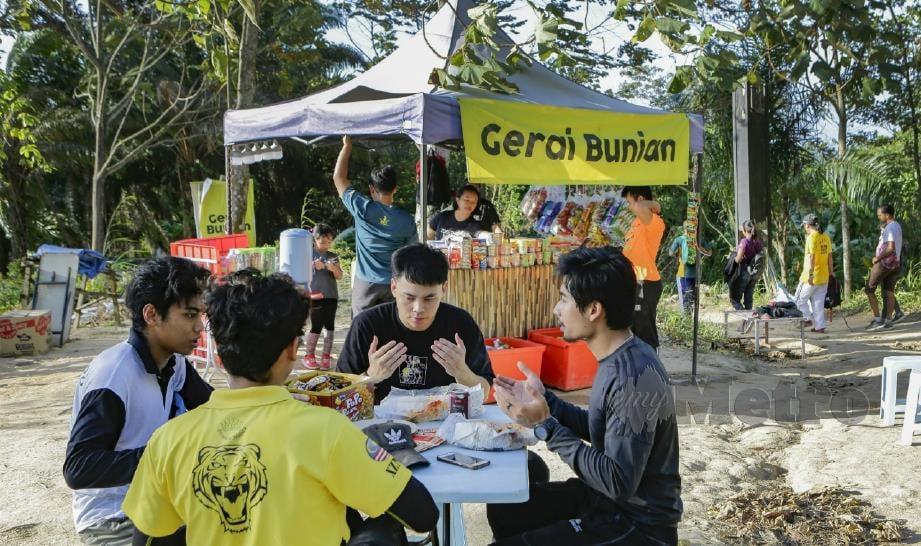 PENDAKI tidak melepaskan peluang berehat di Gerai Bunian milik Arman selepas mendaki Bukit Broga di Semenyih. FOTO Aizuddin Saad.