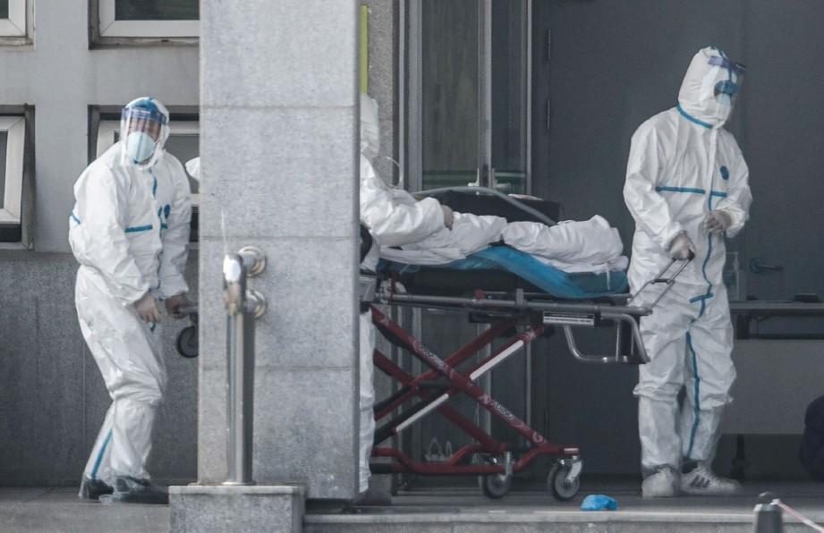 PETUGAS kesihatan menolak pesakit yang dijangkiti wabak ke Hospital Jinyintan. FOTO AFP.