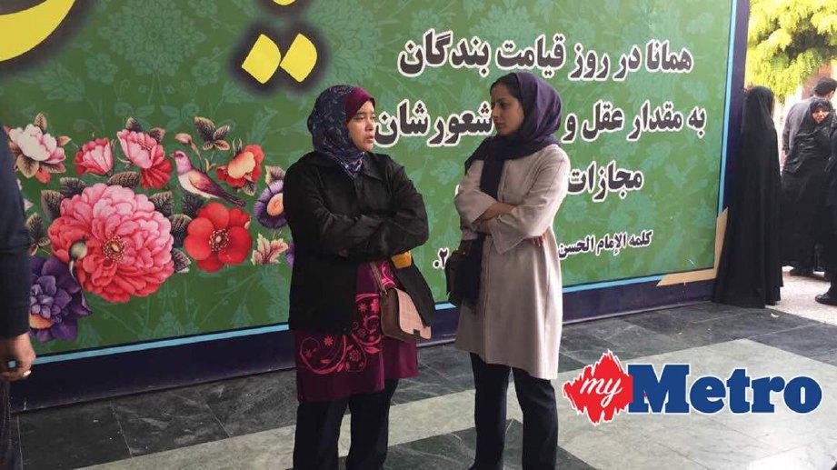 Roslida (kiri) bersama seorang kakitangan Kedutaan Malaysia di Iran menunggu di luar pekarangan rumah mayat di Kahrizak, Tehran, Iran, untuk pengecaman jenazah Ramli.