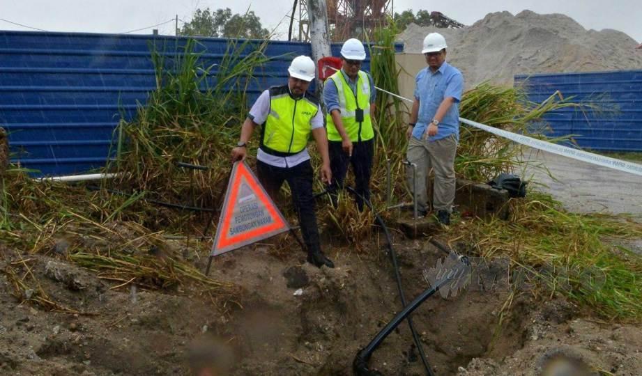 MOHD Fazil (kiri) menunjukkan sambungan bekalan air tidak sah sebuah kilang simen ketika operasi penguatkuasaan di Jalan Sungai Chandong, Pulau Indah, Pelabuhan Klang. FOTO Faiz Anuar